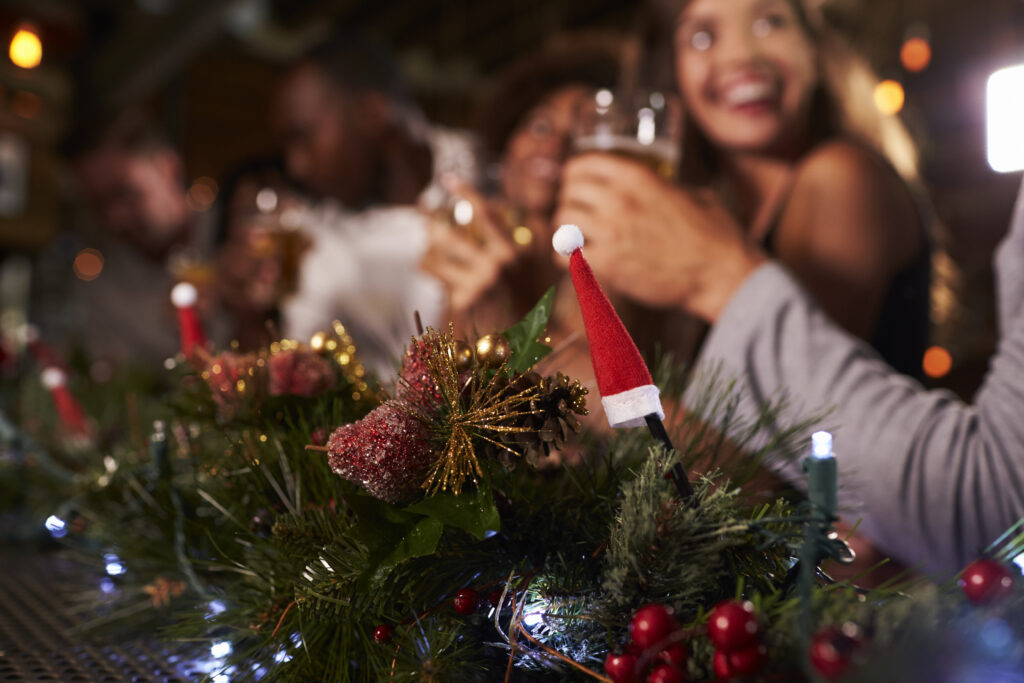 Holiday festive party-goers enjoying drinks and the Christmas decorations