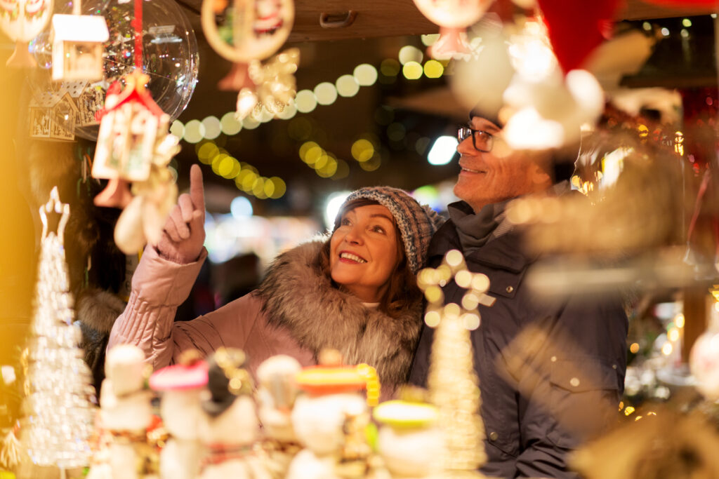 Couple in outside Christmas market looking at lights and gifts