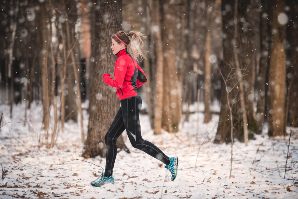 Girl in pink and black running in snow